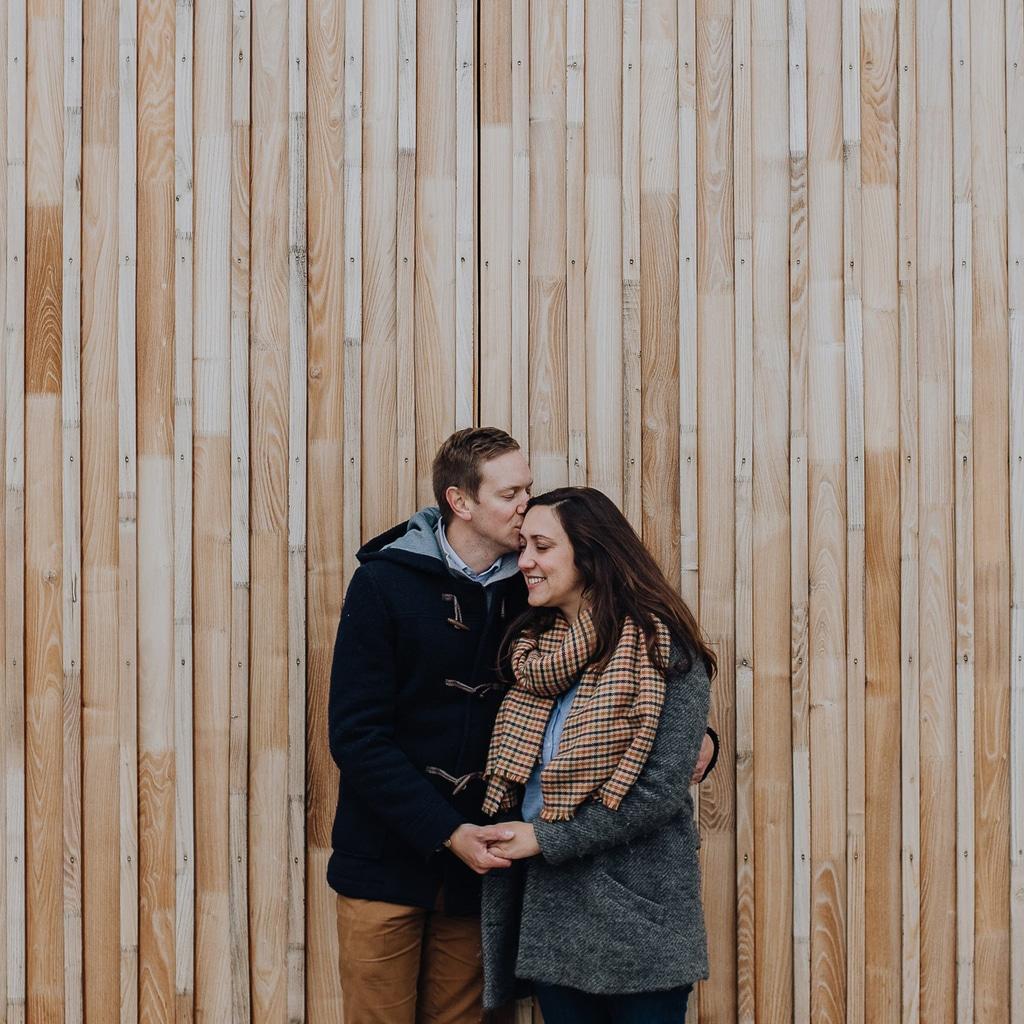 photo d'un couple qui s'aime devant un mur de bois clair